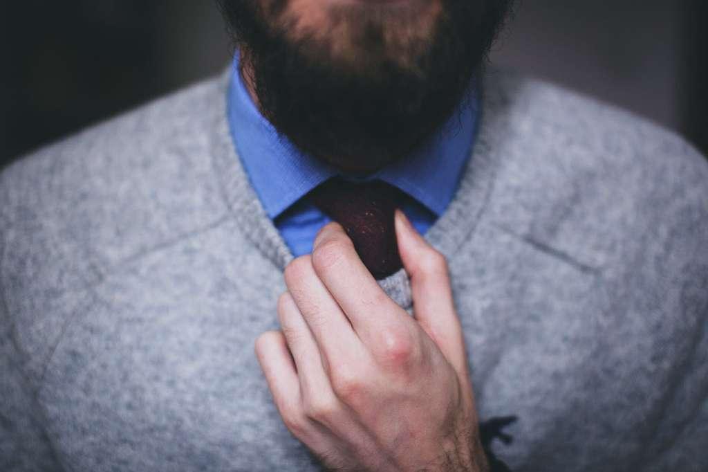 На фото бородатый мужчина поправляет галстук.